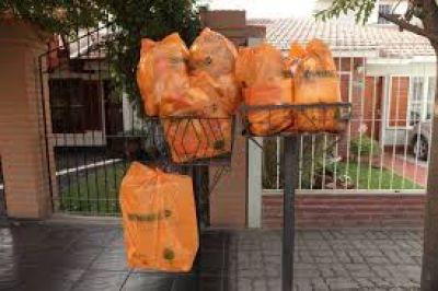 Puesto fijo de distribución de bolsas naranjas para vecinos de Tres Cerritos